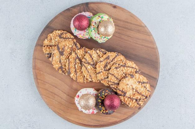 大理石の背景のボード上のクッキーと安物の宝石で覆われたドーナツの束。