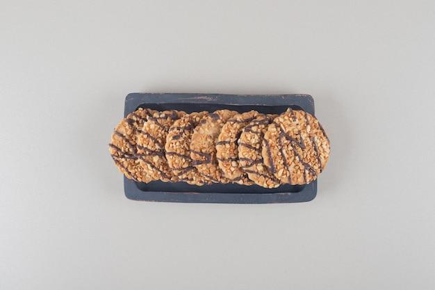 大理石の背景に木製の大皿にクッキーの束。