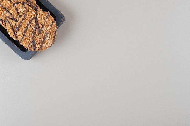 대리석 배경에 나무 플래터에 쿠키 번들.