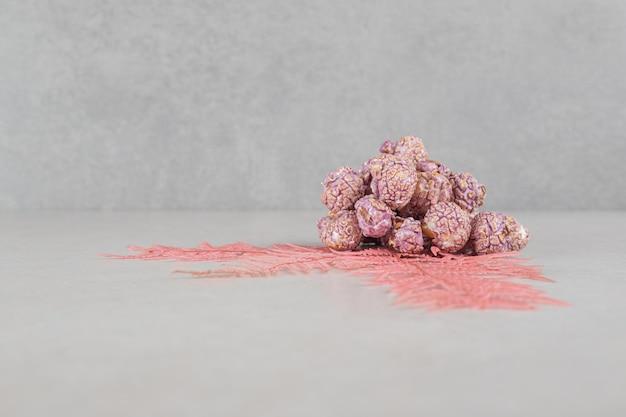 Связка декоративных листьев, украшающих небольшую кучу конфет попкорна на мраморном столе.