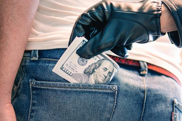 청바지 뒷주머니에 있는 달러 뭉치와 그것을 꺼내는 손. 검은 장갑을 낀 손이 뒷주머니에서 돈을 꺼냅니다. 경범죄와 절도의 개념.