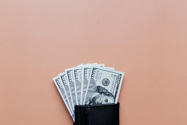Пачка долларов в кошельке на бежевом фоне. фото высокого качества