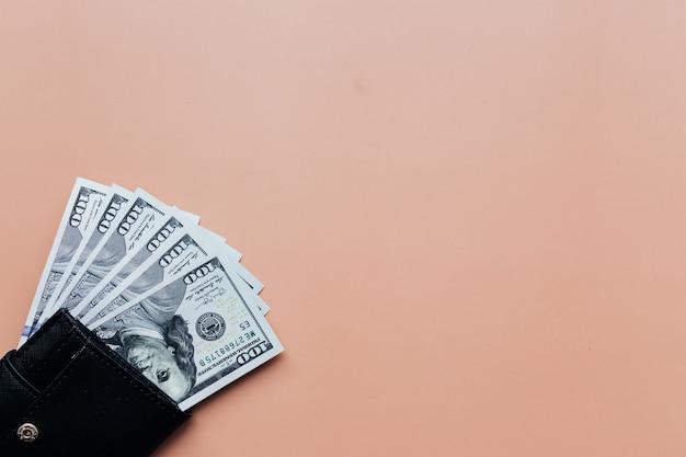 Пачка долларов в кошельке на бежевом фоне