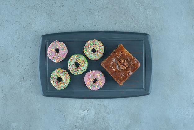 Связка пончиков и кусок пахлавы на темно-синей доске на мраморной поверхности