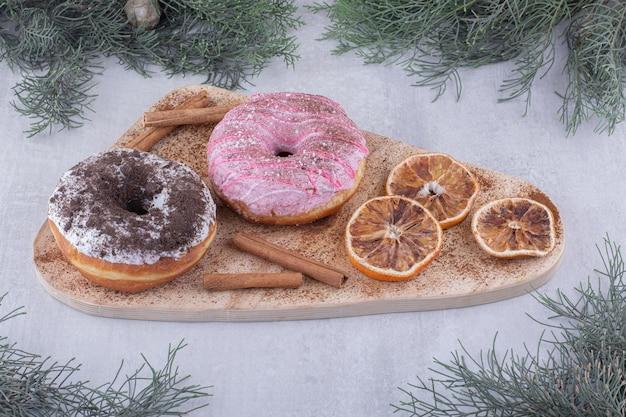 白い表面のボード上の乾燥したオレンジスライス、ドーナツ、シナモンスティックの束