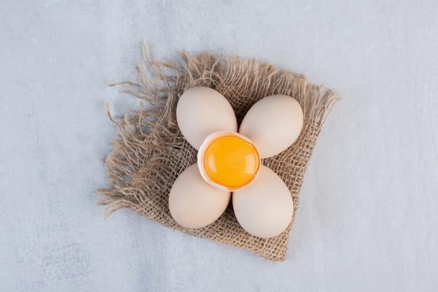 Связка яиц и яичного желтка в скорлупе на мраморном столе.