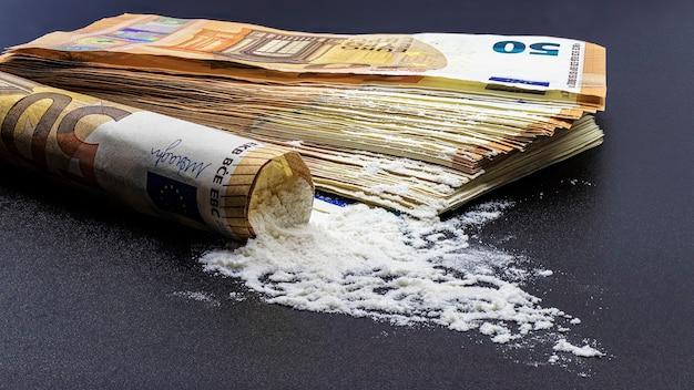 검정색 배경에 유로 지폐와 마약 헤로인 또는 코카인 묶음. 범죄와 마약 퇴치의 개념.