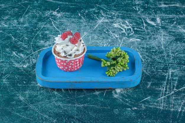 青い背景の上の木製の大皿に花のつぼみとカップケーキの束。高品質の写真