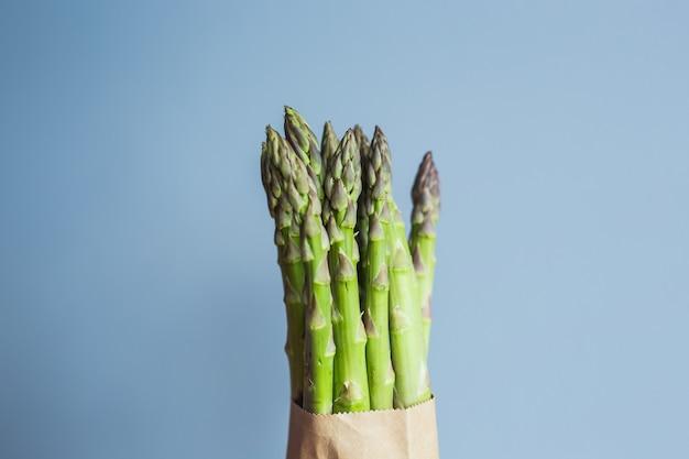 ビーガン菜食主義者と健康食品の青い背景の概念にグリーンアスパラガスのバンドル