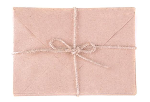 白い孤立した背景にクラフト紙の封筒の束。メールのコンセプト。上面図