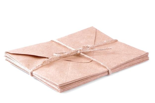 白い孤立した背景にクラフト紙の封筒の束。メールのコンセプト。