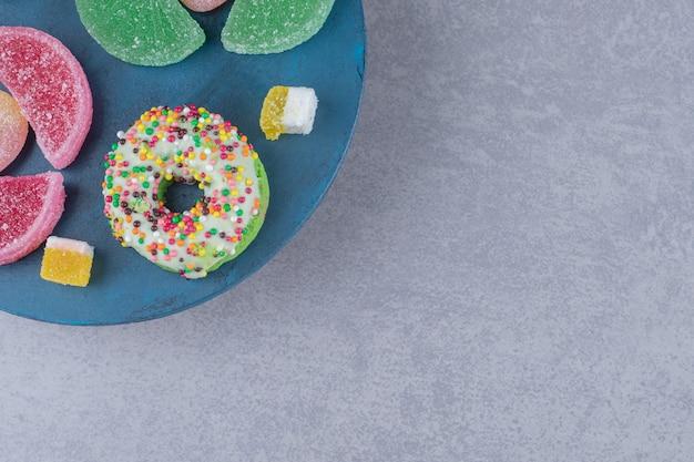 Пачка мармеладов и пончиков на синей доске на мраморной поверхности