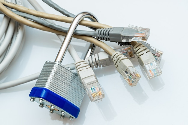 白い背景の上の金属の南京錠でブロックされたネットワークワイヤーの束