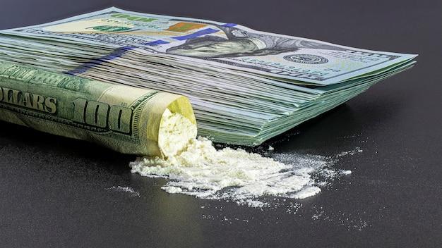 검정색 배경에 100달러 지폐와 마약 헤로인 또는 코카인 묶음. 범죄와 마약 퇴치의 개념.