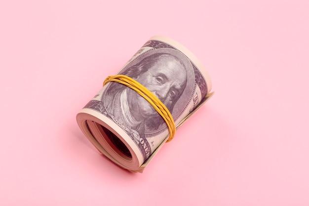 분홍색 최소한의 배경에 100 달러 돈의 번들. 현금 뇌물, 수입 및 이익 개념.
