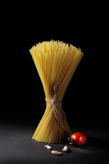 Пачка спагетти из макарон с чесноком и помидорами черри на черном фоне.