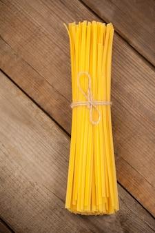 木の表面にロープで結ばれた生のスパゲッティの束
