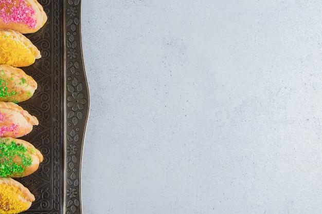 Связка маленьких булочек с различными начинками на декоративном подносе на мраморном фоне.