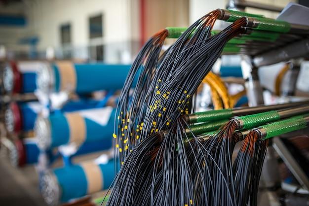 대형 공장 구조용 전자 부품 생산 시 파이프에 전선 묶음이 매달려 있습니다. 개념 제조 산업 부품