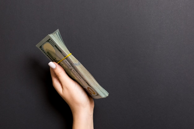 Bundle of one hundred dollar banknotes in female hand on colorful background