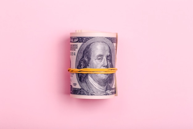 Bundle of one hundred dollar money on a pink minimal background. cash bribe, earnings and profit concept.