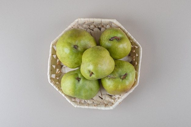 Bundle of pears in a white basket on marble