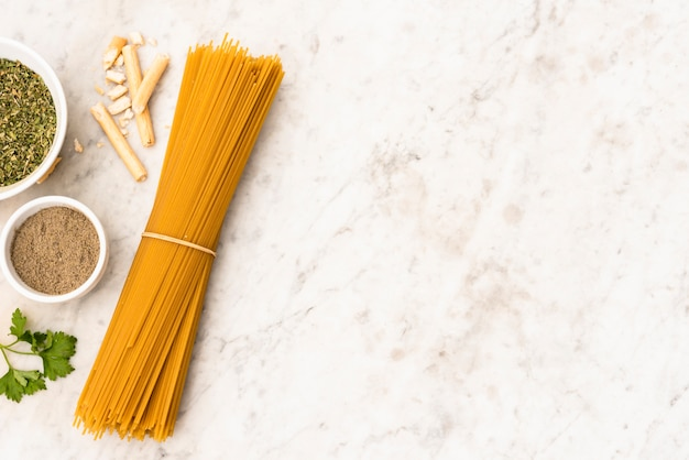 Bundle of uncooked spaghetti pasta and ingredient on marble textured background