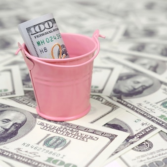 A bundle of us dollars in a metal pink bucket on a set of dollar bills
