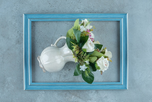 Bundle of white roses in a vase fallen over in the middle of a frame on marble background. high quality photo