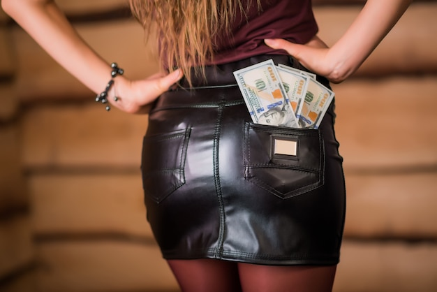 Bundles of banknotes are in the back pocket of the leather skirt of a beautiful young unidentified woman. the concept of prostitution and escort. dishonest money making