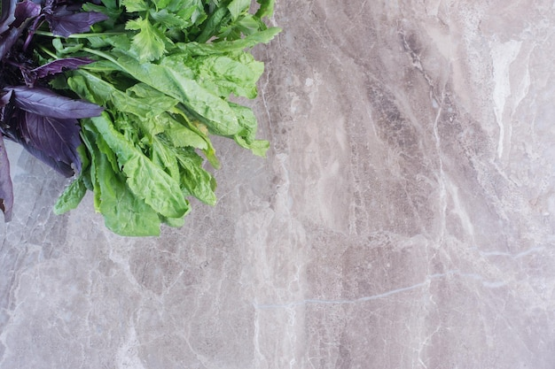 Bundles of basil and amaranth on marble surface