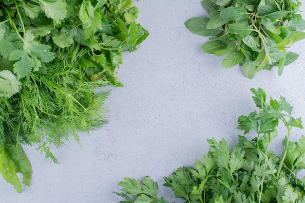Bundles of mint, parsley, coriander and dill on marble background.