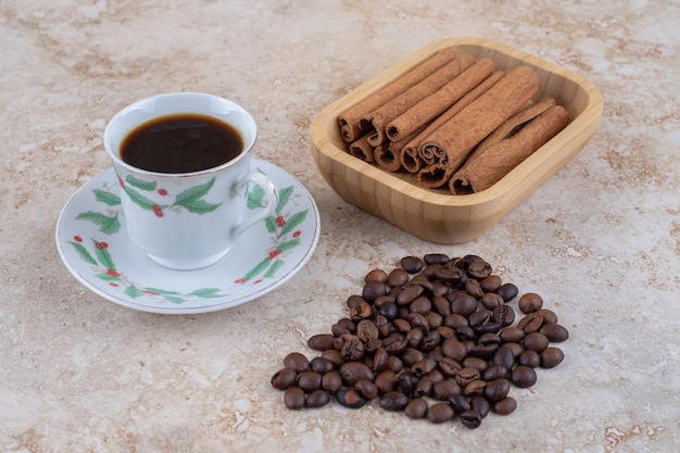 一杯のコーヒーの横にあるシナモンスティックとコーヒー豆の束