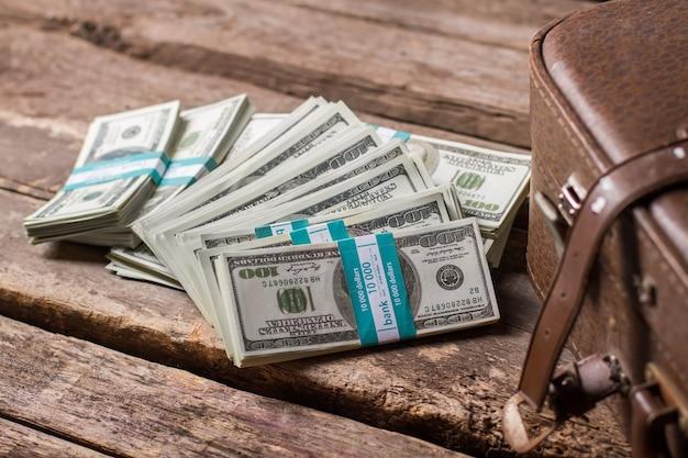 Связки долларов и футляр. коричневый чемодан около американских долларов. билеты в будущее. шанс на всю жизнь.