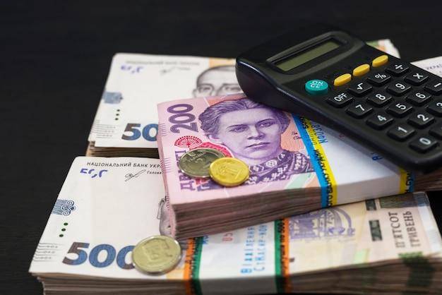 黒い木製のテーブルにグリブナと電卓の束。 200および500グリブナの宗派のウクライナのお金。財務コンセプト。