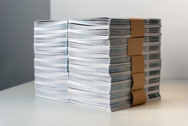 Пачки недавно отпечатанных каталогов, скрепленные оберточной бумагой, аккуратно сложены стопкой на белом столе.
