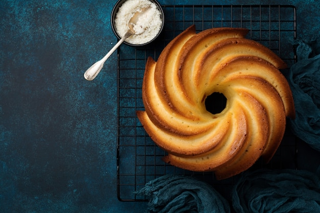 紺色の古いコンクリートの表面に砂糖釉薬とココナッツが入ったバントケーキ。セレクティブフォーカス。