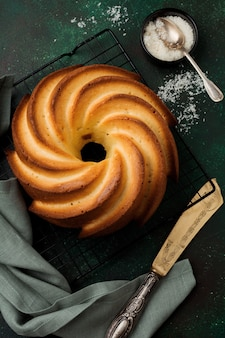 濃い緑色の古いコンクリートの表面に砂糖釉薬とココナッツが入ったバントケーキ。セレクティブフォーカス。上面図