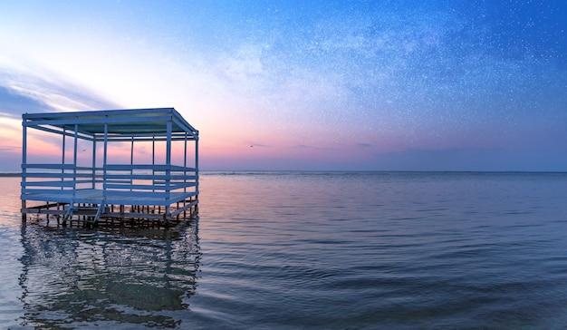 明るい夕日を背景に、水上でリラックスできるバンガロー。オレンジ色の空が澄んだ海に映っています。観光やレクリエーションに最適な場所です。