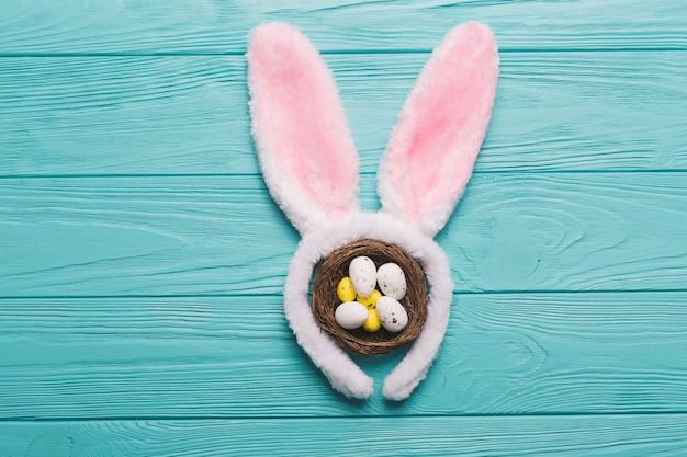 Bunny ears and nest on wooden background