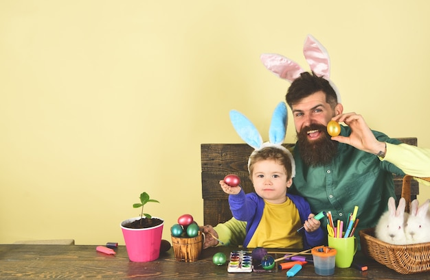 Bunny ears and rabbit ears design father and kid painting easter eggs