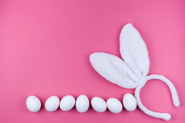 Bunny ears with white eggs on pink background