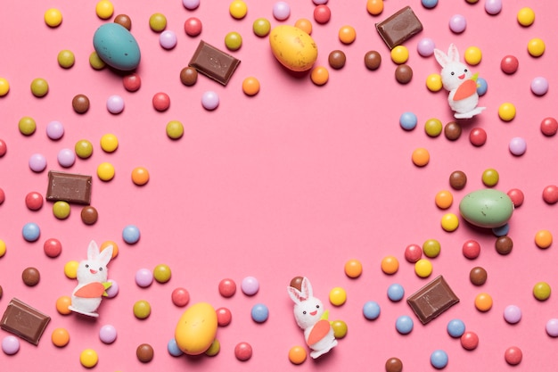 Bunny figurine; gem candies; chocolate easter eggs with space in the center on pink background