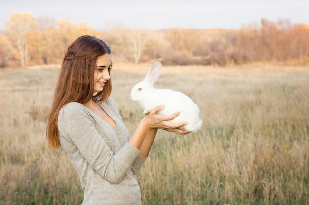 イースターのウサギとかわいいふわふわbunny.friendshipを保持しているrabbit.happy小さな女の子を持つ少女
