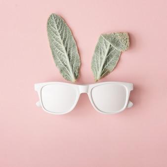 パステルピンクのサングラスと自然な緑の葉で作られたバニーウサギの顔。ハッピーイースターの最小限のコンセプト。