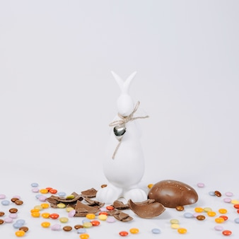 Bunny statuette near chocolate egg and pellets