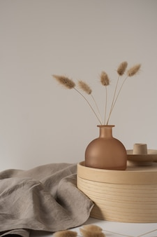 Bunny tail grass in beautiful brown tan vase, wooden storage box, neutral beige blanket on white wall