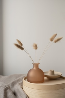 Bunny tail grass in beautiful tan vase, wooden storage box, neutral beige blanket against white wall.
