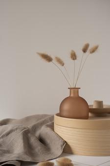 美しい茶色の黄褐色の花瓶、木製の収納ボックス、白い壁にニュートラルベージュの毛布のバニーテールグラス