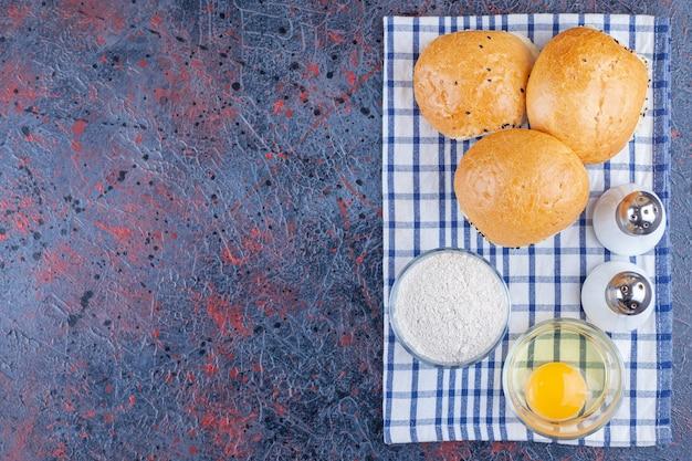 Булочки, миска с мукой и миска с яйцом на кухонном полотенце, на синем столе.